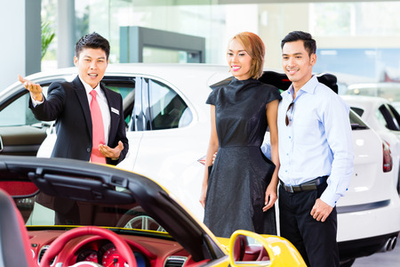 auto dealership: Asian couple buying car in auto dealership consulting the salesman Stock Photo