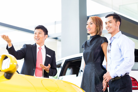 car shop: Asian couple buying car in auto dealership consulting the salesman Stock Photo