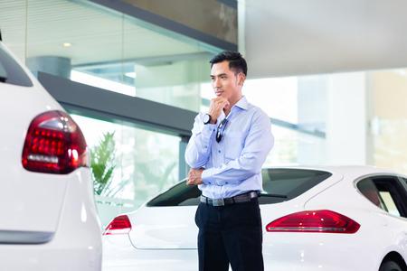 automobile dealer: Asian man buying luxury car in dealership