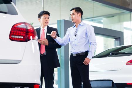 Asian Car Salesman selling auto to customer Stock Photo