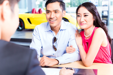 car dealership: Asian Couple signing sales contract for car at dealership Stock Photo