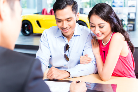 Asian Couple signing sales contract for car at dealership Imagens