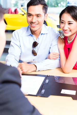 auto leasing: Asian Couple signing sales contract for car at dealership Stock Photo