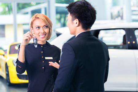 Asian man at car rental receiving key photo