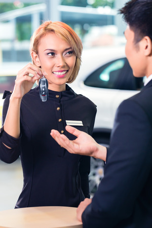 rental: Asian man at car rental receiving key