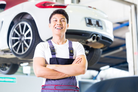 Asian Chinese car mechanic standing in front of luxury car in auto workshop