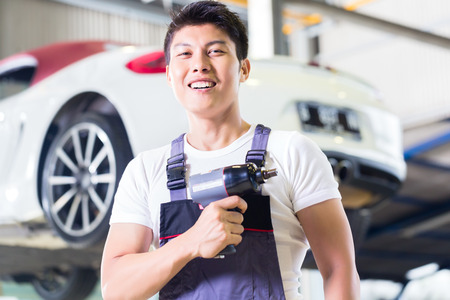 car hoist: Asian Chinese car mechanic with tool in front of luxury car in auto workshop