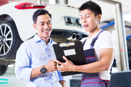 Asian Chinese car mechanic with customer going through the maintenance checklist