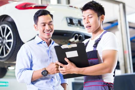 garage automobile: Asie mécanicien automobile chinoise avec le client en passant par la liste de contrôle d'entretien