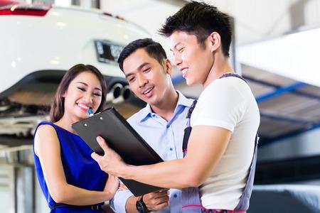 coche: Mecánico de coche y Asia pareja cliente pasando por lista de verificación con el automóvil sobre un elevador en el fondo del taller Foto de archivo