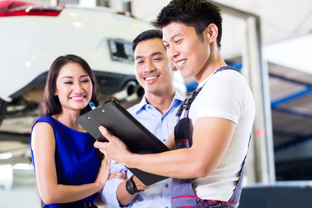 car service: Car mechanic and Asian customer couple going through checklist with auto on hoist in the background of workshop