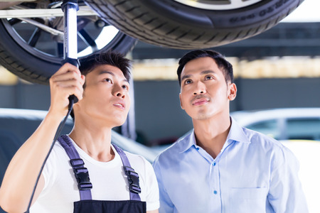 car hoist: Asian Chinese car mechanic with customer looking at auto floor with lamp Stock Photo