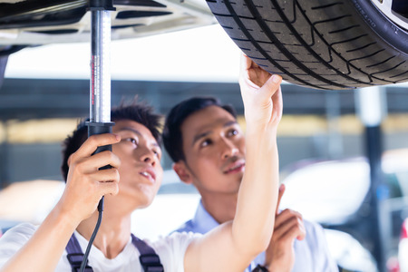 Asian Chinese car mechanic with customer looking at auto floor with lamp Archivio Fotografico