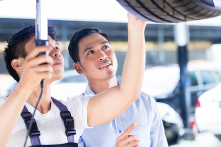 Asian Chinese car mechanic with customer looking at auto floor with lamp photo