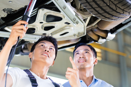 car workshop: Asian Chinese car mechanic with customer looking at auto floor with lamp Stock Photo