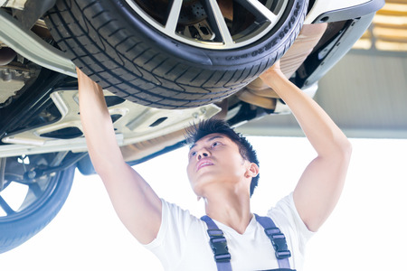 car hoist: Asian Chinese car mechanic changing auto tire