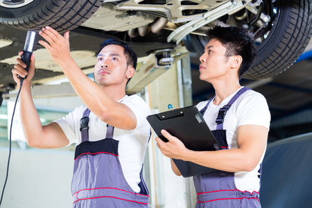 car hoist: Asian Chinese car mechanic with customer going through the maintenance checklist