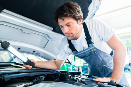 car maintenance: Auto mechanic working in car service workshop Stock Photo