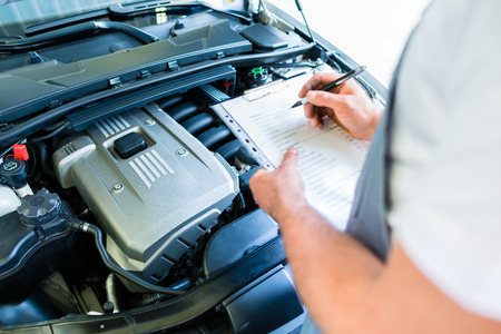 Auto mechanic controlling  car with checklist in workshop 스톡 콘텐츠