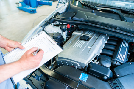 Auto mechanic controlling  car with checklist in workshop Stockfoto