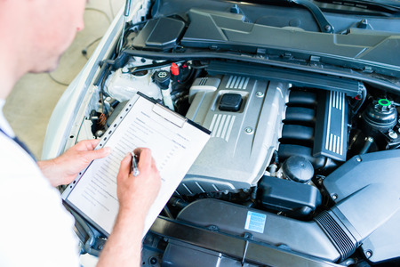 Auto mechanic controlling  car with checklist in workshop photo
