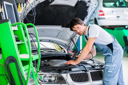 garage automobile: M�canicien avec l'outil de diagnostic dans l'atelier de voiture