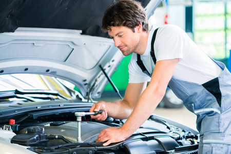 diagnoses: Mechanic with diagnostic tool in car workshop