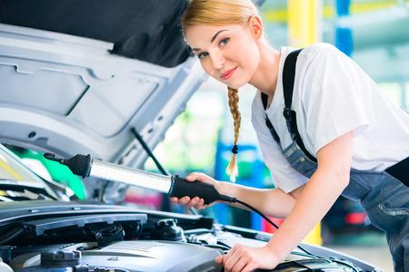 mecanico: Mec�nico de sexo femenino examinar motor del coche con la luz en el taller