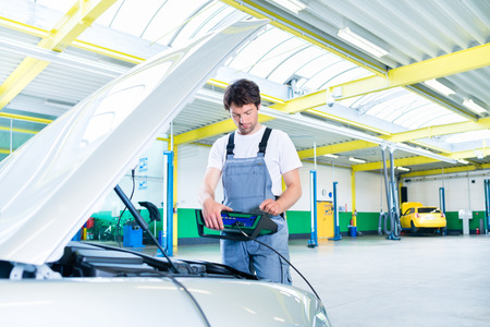 car workshop: Mechanic with diagnostic tool in car workshop