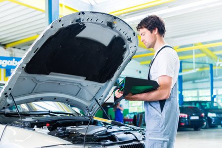 car shop: Mechanic with diagnostic tool in car workshop