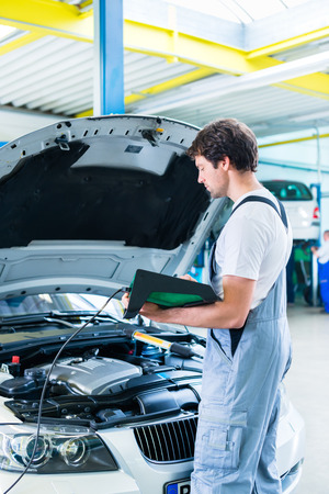 diagnostic tool: Mechanic with diagnostic tool in car workshop