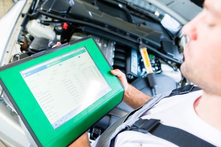 garage automobile: Mécanicien avec l'outil de diagnostic dans l'atelier de voiture