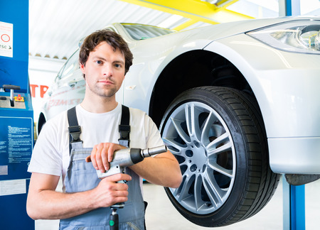 car hoist: Male mechanic changing car tire or tyre in workshop Stock Photo