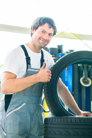 car workshop: Auto mechanic changing tire in car workshop