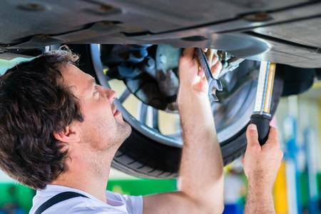 garage automobile: M�canicien travaillant dans l'atelier de voiture sur roues