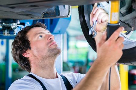 car maintenance: Mechanic working in car workshop on wheel