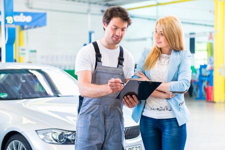 Male workshop mechanic handover car with checklist to client Foto de archivo