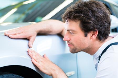男性メカニックへこみや傷のワーク ショップでの車の仕上げを検査します。