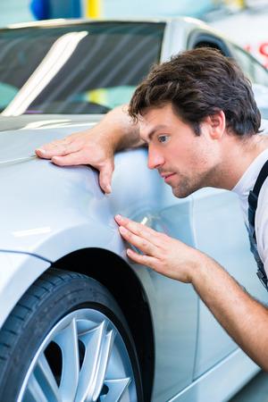 Man monteur onderzoekt auto afwerking op deuken of krassen in de werkplaats Stockfoto