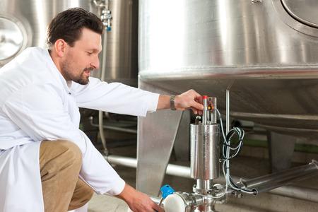 brewer: Cervecero de la cerveza en su cervecer�a en el tanque de alimentaci�n Foto de archivo