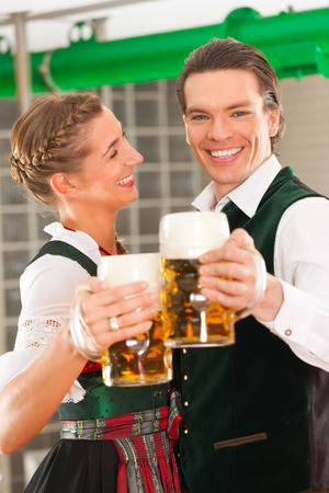 Man and woman with beer glasses in Bavarian tracht in brewery in front of a brew kettle photo