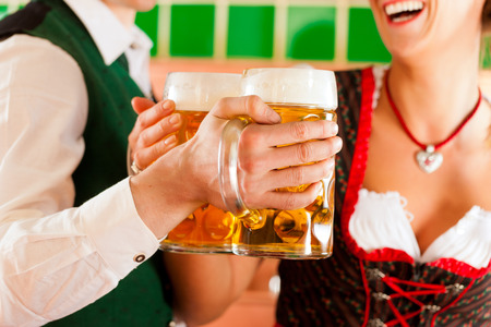 Young man and woman in traditonal Tracht with beer glass in brewery, in front of brewing kettle photo