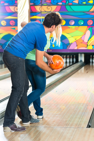 Young couple or friends, man and woman, playing bowling with a ball in front of the ten pin alley, he shows her how it works photo