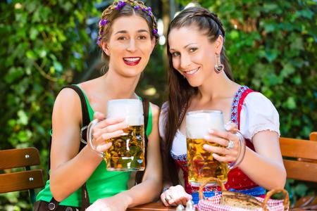 In Beer garden – female friends in Tracht, Dirndl and Lederhosen drinking a fresh beer in Bavaria, Germany photo