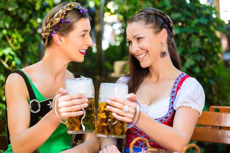 In Beer garden ? female friends in Tracht, Dirndl and Lederhosen drinking a fresh beer in Bavaria, Germany photo