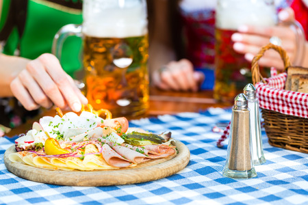 dirndl: In Beer garden - friends in Tracht, Dirndl and Lederhosen with snacks drinking a fresh beer in Bavaria, Germany