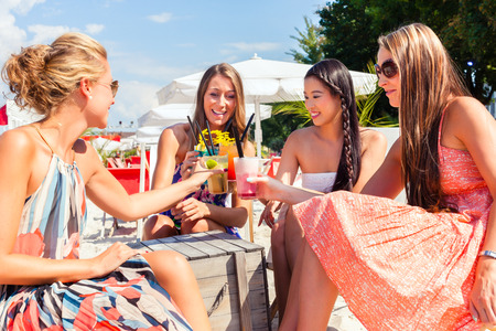 bars: Four woman sitting in beach bar, drinking fancy cocktails and tanning in the sun