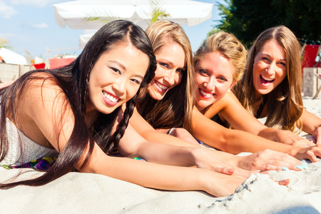 tanning: Four woman lying on beach sand, tanning in the sun Stock Photo