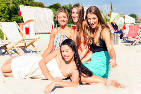 Four woman lying on beach sand, tanning in the sun photo