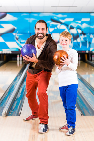 Father and son playing in bowling center photo
